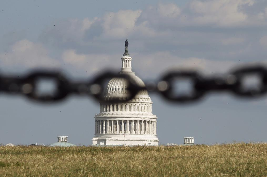 The U.S. Capitol is photographed through a chain fence in Washington, Sept. 30, 2013.