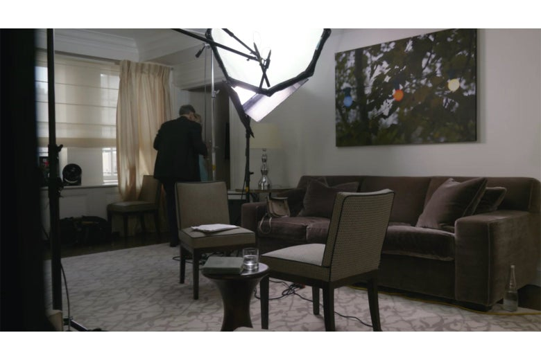A shot from Borat of a hotel living room. Tutar and Rudy Giuliani are walking away from camera toward the hotel bedroom.