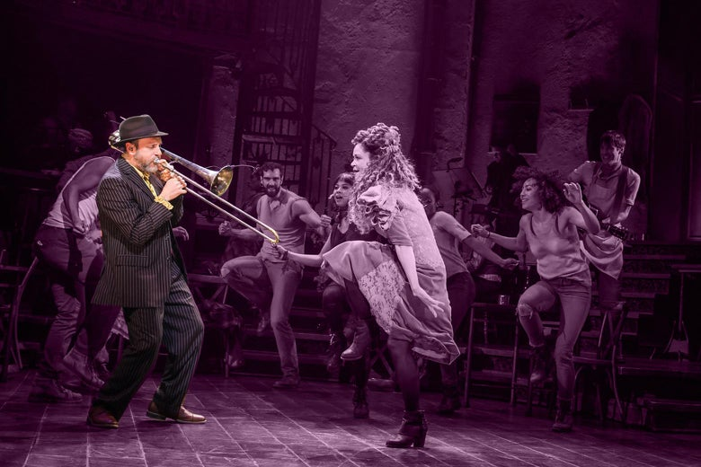 Brian Drye plays trombone with actors dancing around him onstage