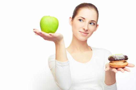 Portrait of young cheerful woman choosing between apple and cake