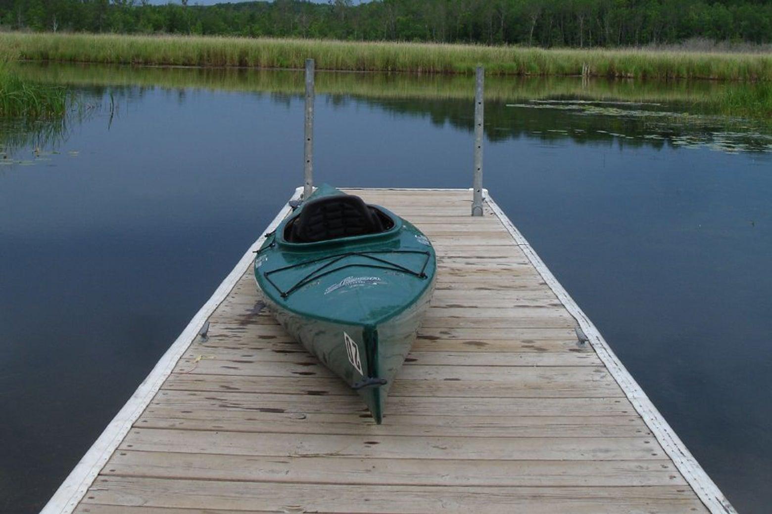 A kayak sitting on a dock.