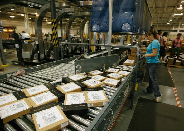 Amazon employee Heather Redman packs Kindles for shipment at the warehouse in Campbellsville, Ky.