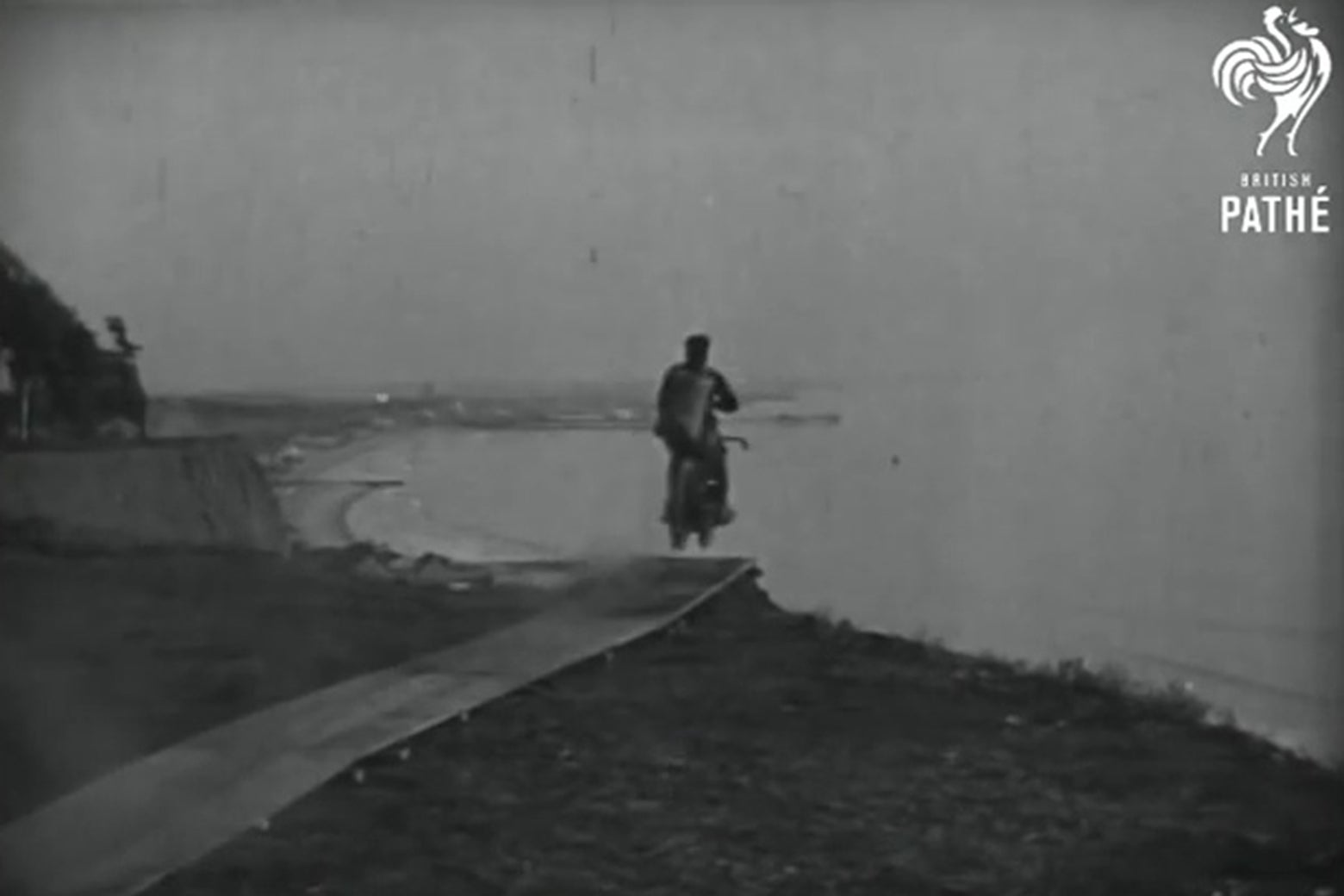 In a still frame from a 1926 newsreel, a man on a motorcycle flies off a cliff.