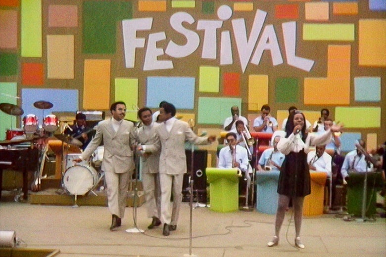 Four artists (three men in suits, one woman in a dress) stand on a stage performing against a multicolored backdrop that reads FESTIVAL.