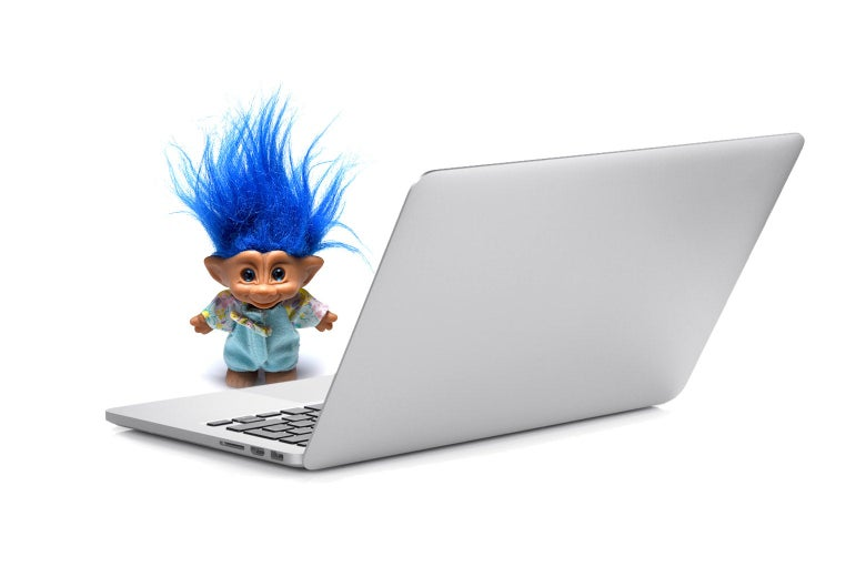 A troll doll is seen in front of a laptop.