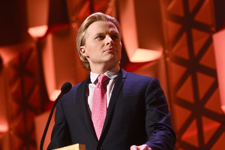 Ronan Farrow behind a podium with a red background.