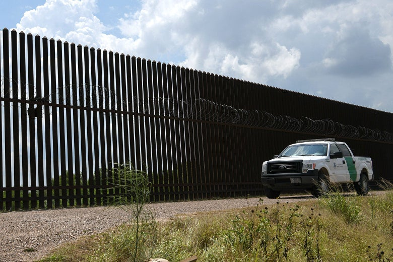 A Border Patrol vehicle drives along a section of border fence near the U.S.-Mexico border on June 12 in Hidalgo, Texas.