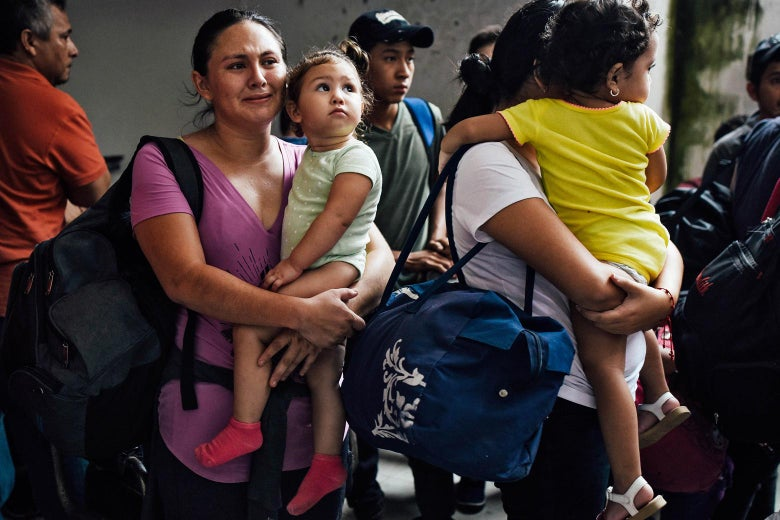 A group of migrants, including two mothers holding children in their arms.
