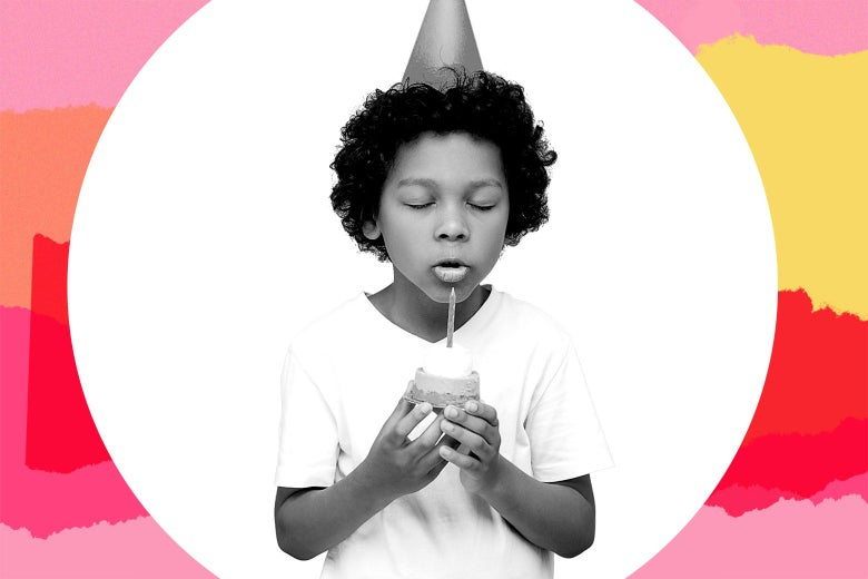 A little boy wearing a birthday hat closing his eyes as he blows out a single candle on a cupcake