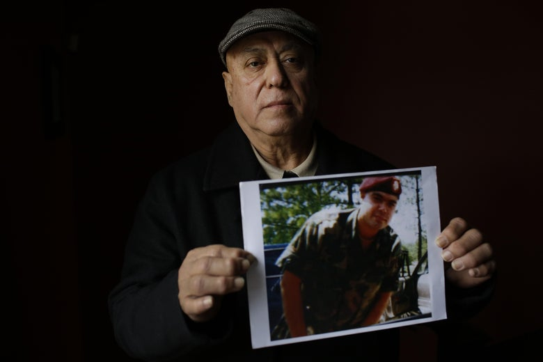 Miguel Perez poses as he holds a photo of his son Miguel Perez Jr., on April 4, 2017 in Chicago, Illinois.Perez Jr., an Army veteran is facing deportation after serving seven years in a state penitentiary on a drug charge.