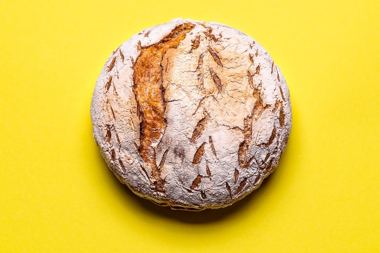 A loaf of leavened bread against a yellow background