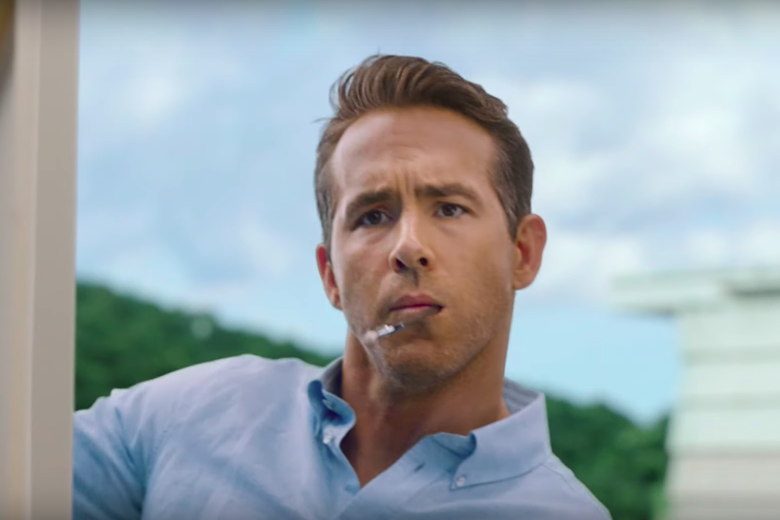 Ryan Reynolds with a paint brush in his mouth.