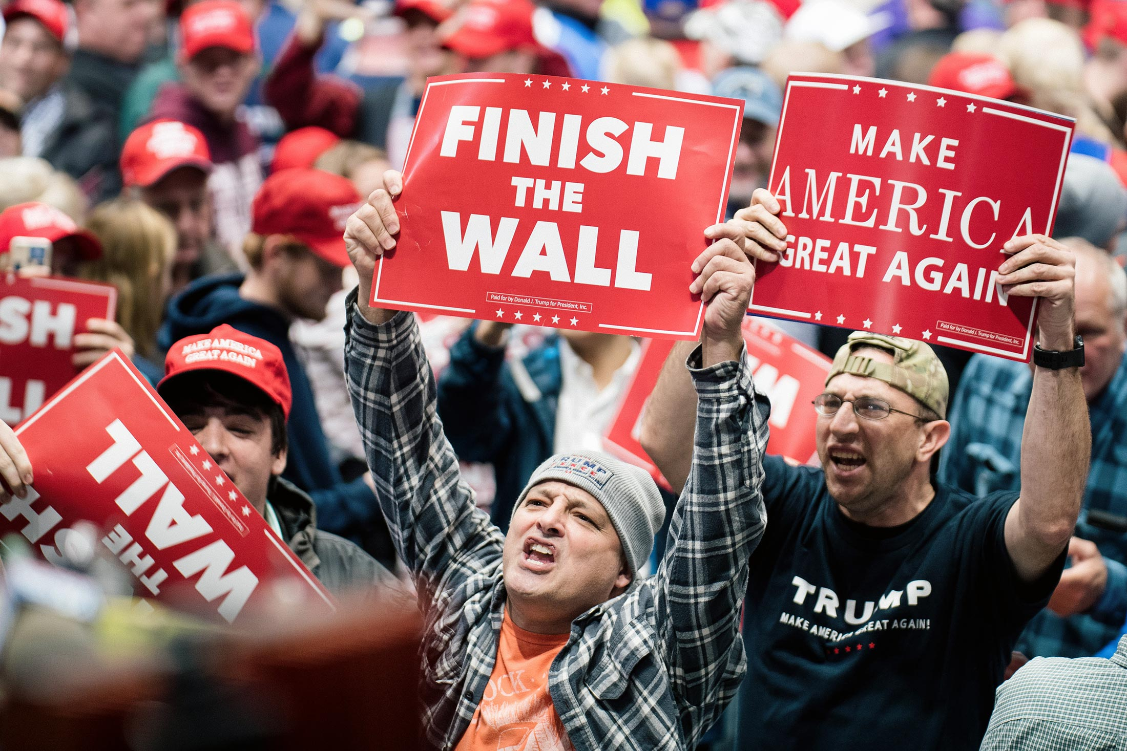 """Supporters shout and hold signs saying things like, """"Finish the wall."""""""