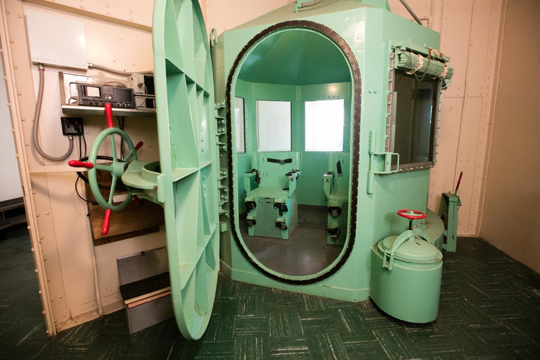 A teal gas chamber with the door open and a big handle like an old-timey safe.