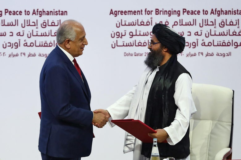 U.S. Special Representative for Afghanistan Reconciliation Zalmay Khalilzad and Taliban co-founder Mullah Abdul Ghani Baradar shake hands after signing a peace agreement during a ceremony in the Qatari capital Doha on February 29, 2020.