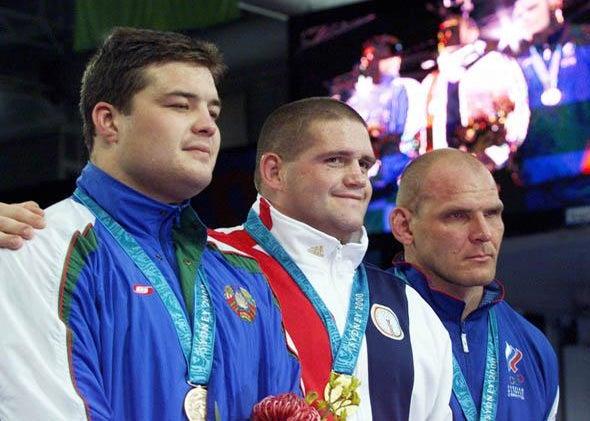 USA's Rulon Gardner (C) stands with his gold medal alongside silver medallist Alexandre Kareline.