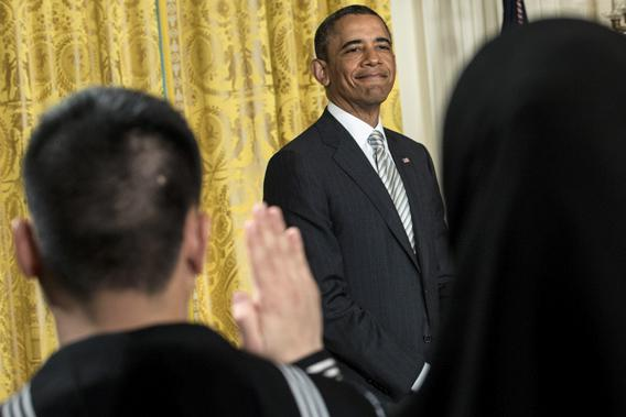 President Obama listens while the oath of allegiance is administered during a naturalization ceremony in the East Room of the White House on March 25, 2013 in Washington.