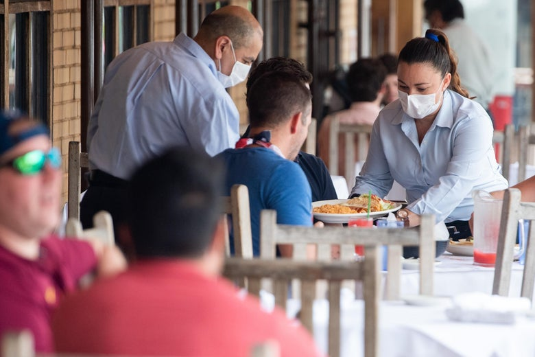A waiter wearing a mask and gloves delivers food to a table to customers seated at an outdoor patio at a Mexican restaurant in Washington, DC, May 29, 2020. - Friday marks the beginning of phase one in the city with restaurants reopening following the stay at home orders from the COVID-19 pandemic, provided they can serve customers outdoors with groups sitting at least 6 feet apart. (Photo by SAUL LOEB / AFP) (Photo by SAUL LOEB/AFP via Getty Images)