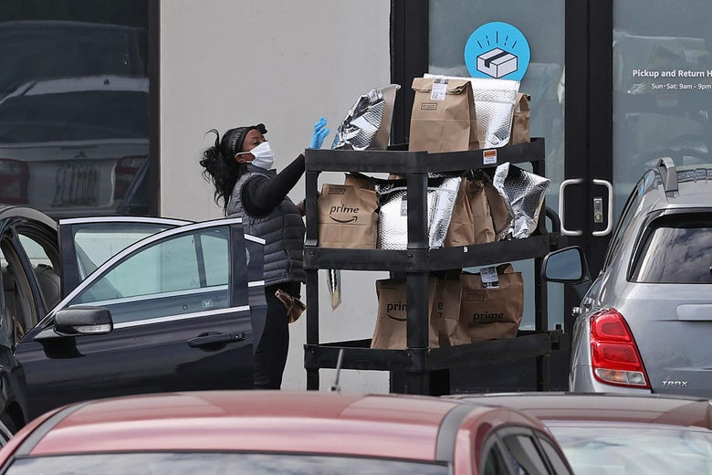 A woman grabs Amazon Prime packages from a cart and loads them into her car.