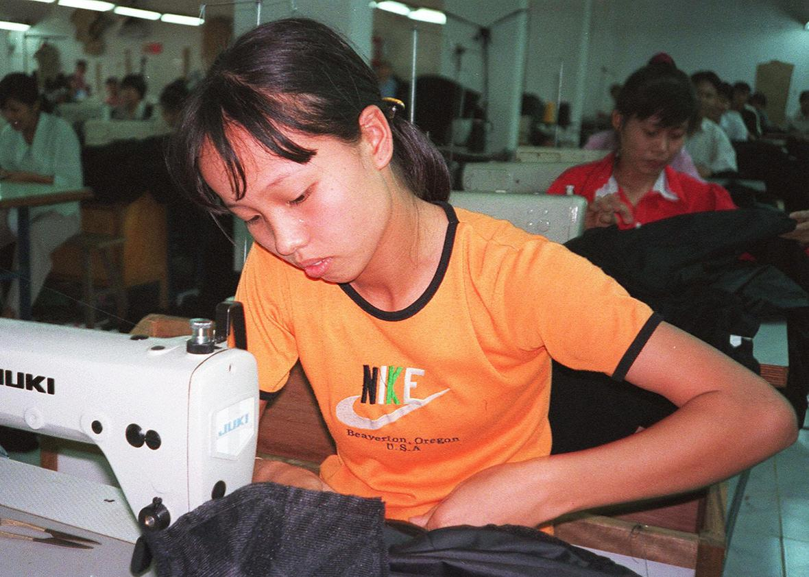 File photo dated 15 October 1998 shows a young female worker stiching together garments for export from Vinh Phat Export Garment Co., a privately owned garment company on the outskirts of Hanoi, Vietnam.