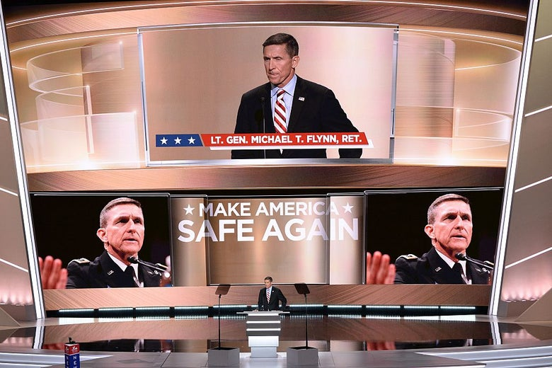 Flynn stands at a lectern as the words MAKE AMERICA SAFE AGAIN and several large images of his face are projected on the huge screen behind him.