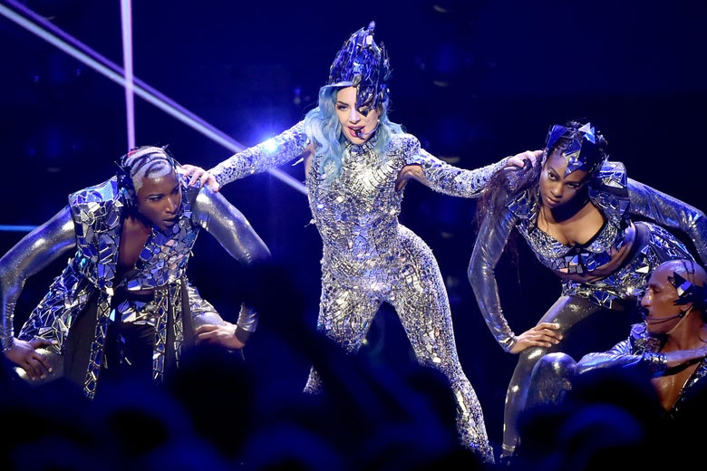 Lady Gaga performs onstage in a sparkling suit with backup dancers.