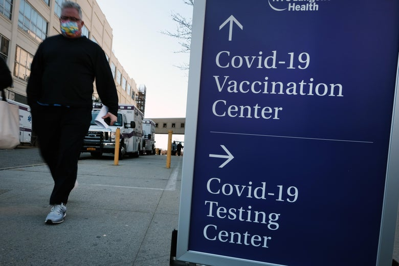 People walk by a sign pointing toward a COVID-19 testing center and a COVID-19 vaccination center at a Brooklyn hospital.