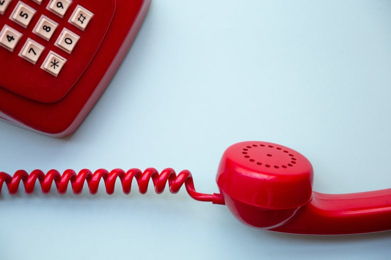 A red corded telephone