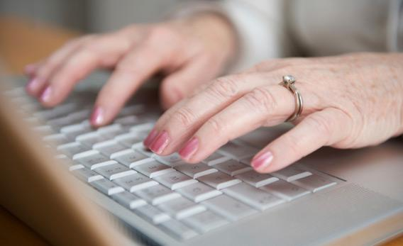 Older woman typing on a laptop.