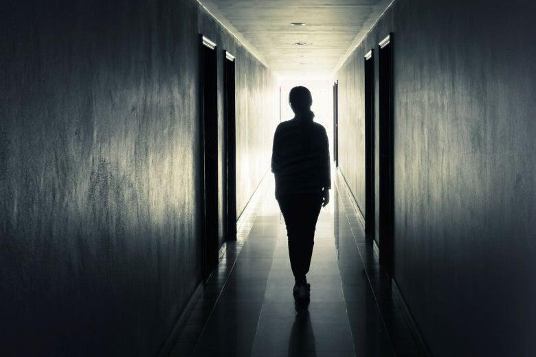 A woman walks down a hallway.