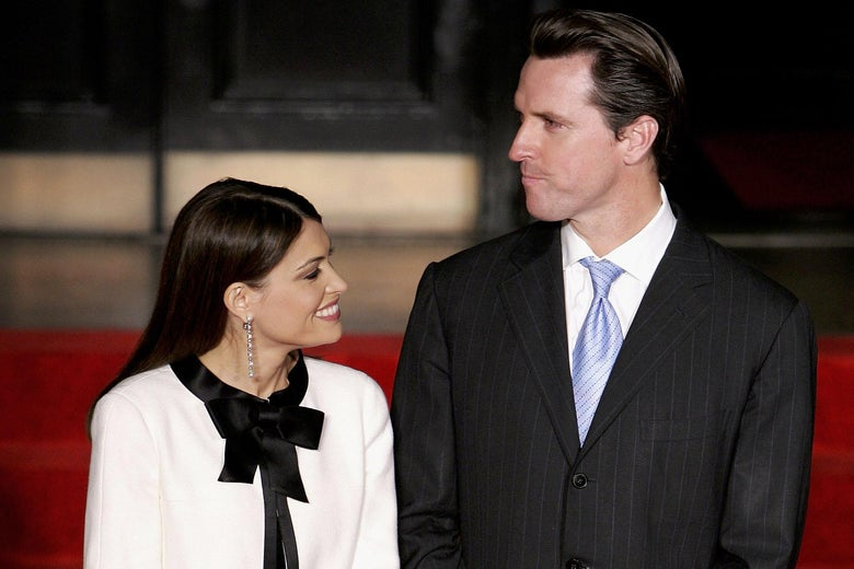 Kimberly Guilfoyle looks up at Gavin Newsom, standing next to her.