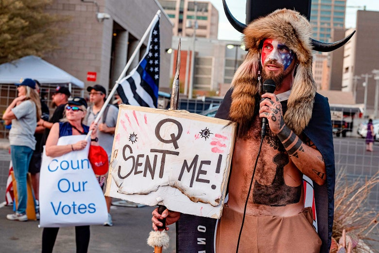 "A man in a fur headdress with horns holds up a sign that says, ""Q sent me,"" as he talks into a microphone."