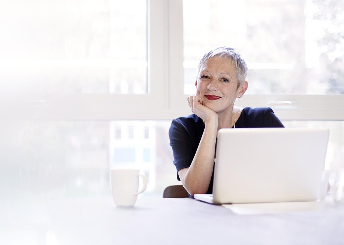 Woman working on laptop, smiling.