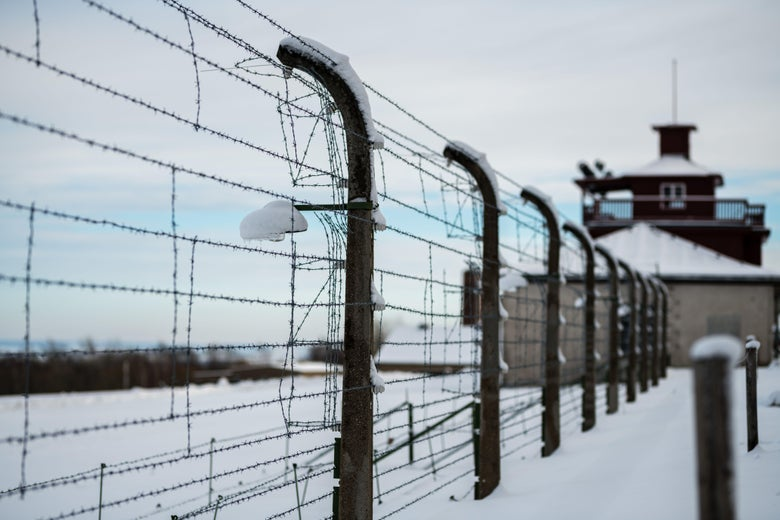 A barbed wire fence encloses the memorial site of the former Nazi concentration camp Buchenwald after snowfall near Weimar, eastern Germany, on January 27, 2021, the International Holocaust Remembrance Day.