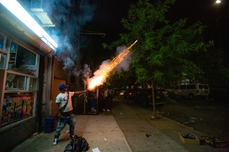 A man in Brooklyn New York holds a firework stick in his hands as it explodes.