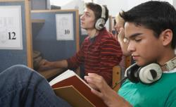 Portrait of two teenage boys wearing headphones in a library