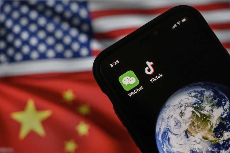A mobile phone showing logos for TikTok and WeChat in front of U.S. and China flags.