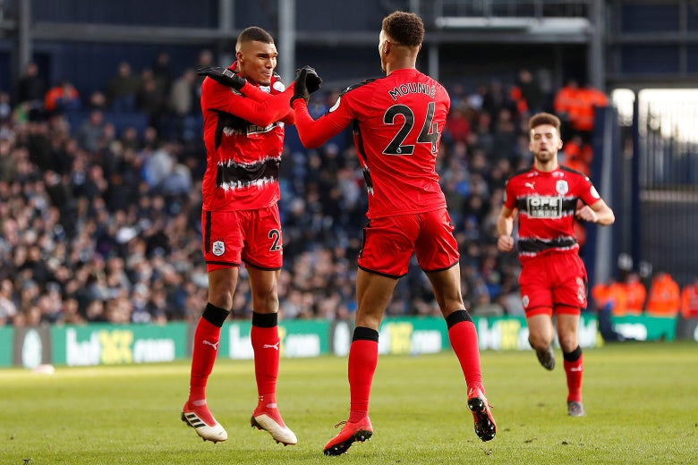 Huddersfield Town soccer players Steve Mounie and Colin Quaner celebrate a goal against West Bromwich Albion with the Wakanda salute, Feb. 24.