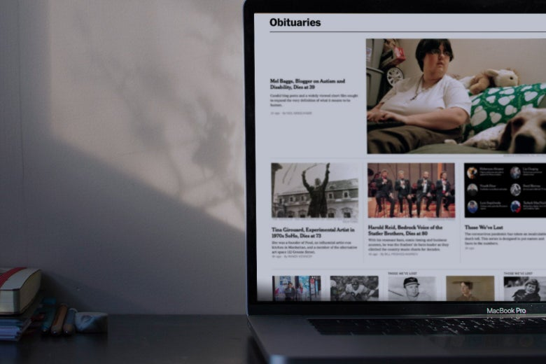 The New York Times Obituaries page on a laptop on a desk.