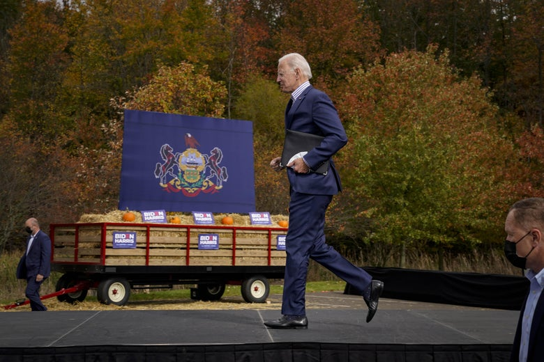 Joe Biden jogs offstage, with a cart full of hay in the background
