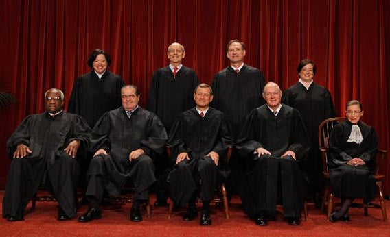 U.S. Supreme Court members pose for photographs.