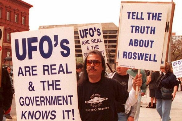 A man carries signs espousing UFO conspiracy theories.