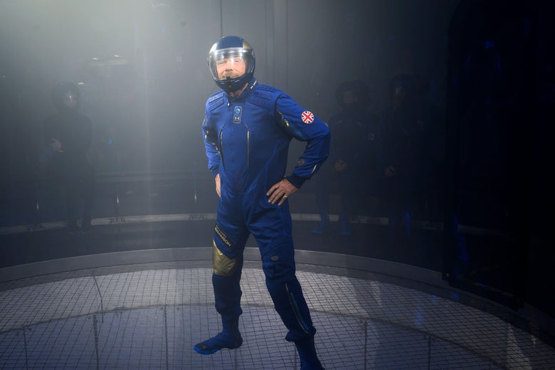 A man in a blue jumpsuit and helmet stands with his hands on his hips.