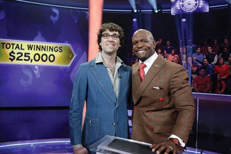"Terry Crews has his arm around Justin Peters on the set of Millionaire. Behind them, the studio audience and a screen that says ""TOTAL WINNINGS $25,000."""