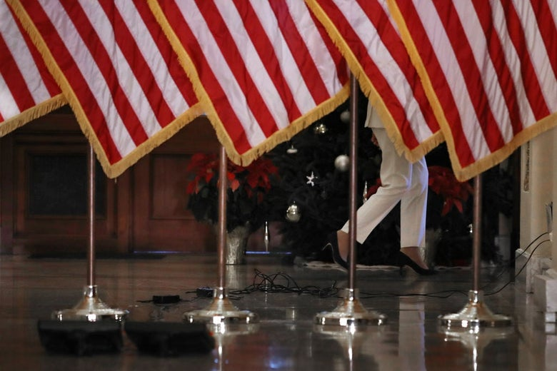 Pelosi's legs and feet are seen from underneath a row of American flags.