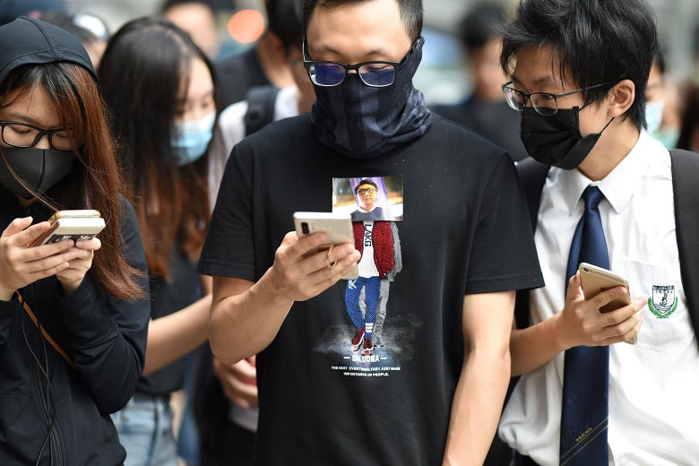 Protesters, wearing masks to cover their faces, look at their smartphones.