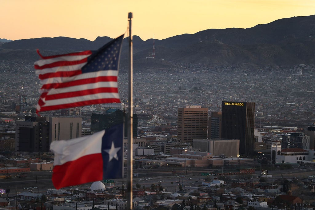 U.S. and state of Texas flags fly in the foreground as the cities of El Paso and Juarez stretch into the distance backdropped by mountains.