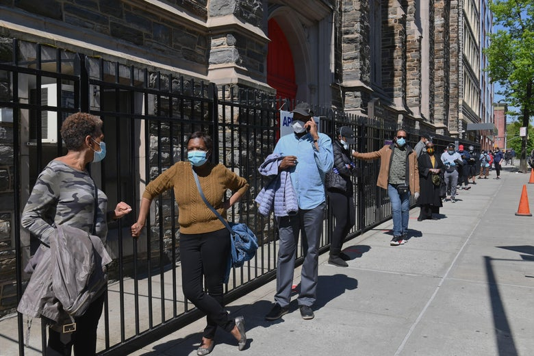people stand in a line, far apart, wearing masks