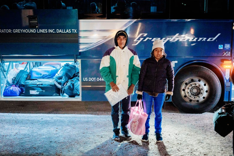 A man and his daughter stand in front of a Greyhound bus.