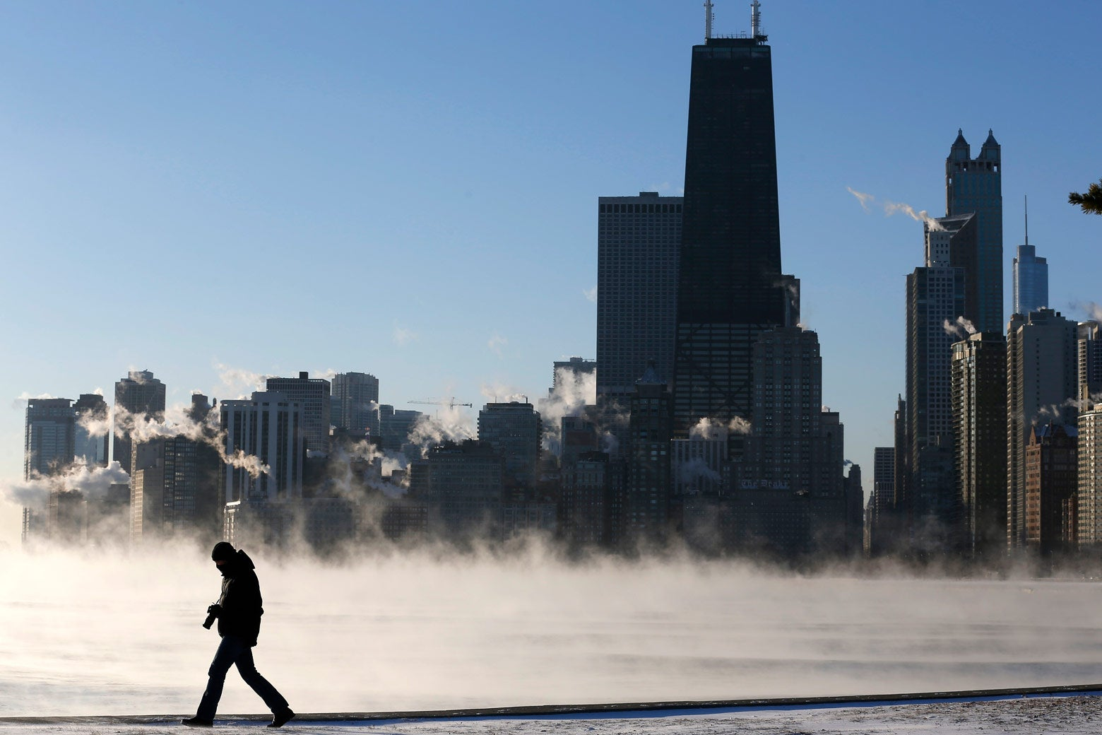 A man is silhouetted against the smoke rising off Lake Michigan.